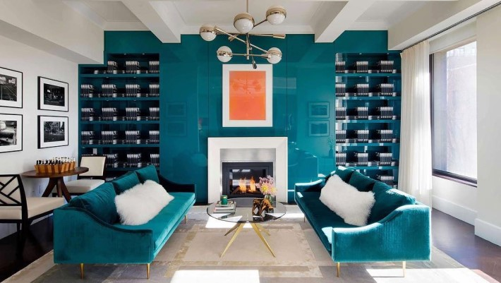 A living room with teal blue sofas and a blue lacquered wall with a gold and glass cocktail table and a gold and white contemporary chandelier - room colors and moods - blue psychology